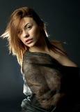 Ritratto biondo scuro provocatorio della ragazza sopra la luce nera della parte posteriore del fondo fotografia stock libera da diritti