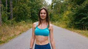 Ritratto casuale della donna attraente del pareggiatore che cammina al parco Corridore atletico della ragazza all'aperto stock footage