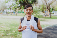 Ritratto che un uomo con l'asciugamano bianco che riposa dopo lo sport di allenamento si esercita all'aperto al parco pubblico, s Fotografie Stock
