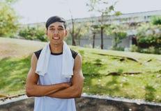 Ritratto che un uomo con l'asciugamano bianco che riposa dopo lo sport di allenamento si esercita all'aperto al parco pubblico, s Immagini Stock Libere da Diritti