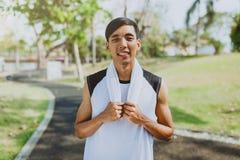 Ritratto che un uomo con l'asciugamano bianco che riposa dopo lo sport di allenamento si esercita all'aperto al parco pubblico, s Fotografia Stock Libera da Diritti