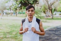 Ritratto che un uomo con l'asciugamano bianco che riposa dopo lo sport di allenamento si esercita all'aperto al parco pubblico, s Fotografia Stock