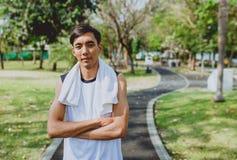 Ritratto che un uomo con l'asciugamano bianco che riposa dopo lo sport di allenamento si esercita all'aperto al parco pubblico, s Immagini Stock