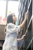 Ritratto cinese di giovane bella donna che raggiunge per un libro delle biblioteche in libreria Fotografia Stock Libera da Diritti