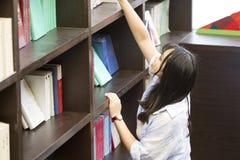 Ritratto cinese di giovane bella donna che raggiunge per un libro delle biblioteche in libreria Immagini Stock