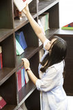 Ritratto cinese di giovane bella donna che raggiunge per un libro delle biblioteche in libreria Fotografia Stock