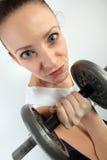 Ritratto comico di una donna che tiene un grande dumpbell per l'allenamento di sollevamento di peso Immagini Stock