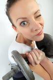 Ritratto comico di una donna che tiene un grande dumpbell per l'allenamento di sollevamento di peso Fotografia Stock