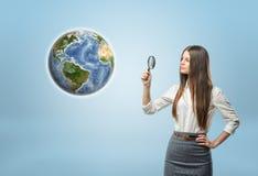 Ritratto completo della donna di affari che esamina la terra del globo tramite una lente Immagine Stock Libera da Diritti