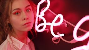 Ritratto creativo di bella ragazza vicino alla parete leggera al neon rossa stock footage