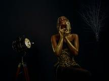 Ritratto creativo surreale del modello afroamericano sexy con la parrucca lucida dell'oro e del trucco che posa alla macchina fot Immagini Stock Libere da Diritti