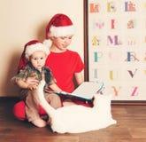 Ritratto d'annata dei ragazzi in cappelli di Santa che leggono un libro di Natale Fotografie Stock
