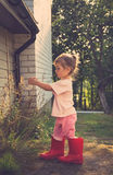 ritratto d'annata della bambina sveglia che cammina negli stivali rossi Immagine Stock