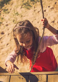 Ritratto d'annata di poca ragazza sveglia della scuola in vestito rosso divertendosi e giocando all'aperto nel giorno di estate Fotografia Stock