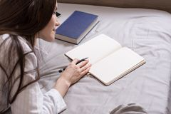 Ritratto dal retro di una donna castana che si trova a letto con un libro e un diario, annotazioni Concetto-pianificazione, desid Fotografie Stock