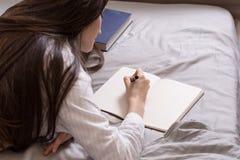 Ritratto dal retro di una donna castana che si trova a letto con un libro e un diario, annotazioni Concetto-pianificazione, desid Immagini Stock Libere da Diritti
