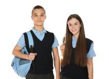 Ritratto degli adolescenti in uniforme scolastico con gli zainhi su bianco fotografia stock libera da diritti