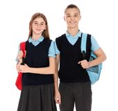 Ritratto degli adolescenti in uniforme scolastico con gli zainhi immagini stock