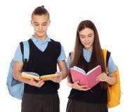 Ritratto degli adolescenti in uniforme scolastico con i libri e gli zainhi su bianco fotografia stock libera da diritti
