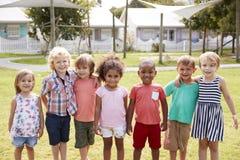 Ritratto degli allievi alla scuola di Montessori durante la pausa all'aperto Fotografie Stock Libere da Diritti