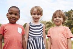 Ritratto degli allievi alla scuola di Montessori durante la pausa all'aperto Immagine Stock Libera da Diritti