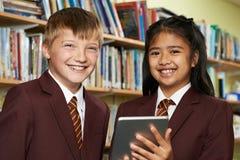 Ritratto degli allievi che portano uniforme scolastico facendo uso della compressa I di Digital Immagini Stock