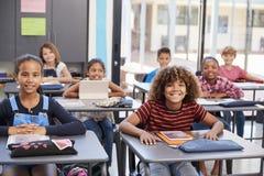 Ritratto degli allievi della scuola elementare che si siedono ai loro scrittori Fotografia Stock