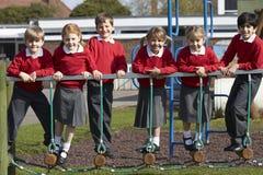 Ritratto degli allievi della scuola elementare su attrezzatura rampicante Immagini Stock