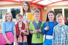 Ritratto degli allievi della scuola fuori dell'aula con l'insegnante Immagini Stock