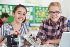 Ritratto degli allievi femminili che studiano robotica nella lezione di scienza Immagini Stock