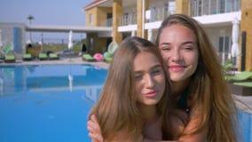 Ritratto degli amici di ragazze felici, della giovane donna sveglia con capelli lunghi e di bella pelle che si abbraccia feliceme video d archivio
