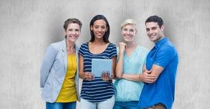 Ritratto degli amici felici con la compressa digitale contro fondo grigio immagine stock