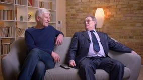 Ritratto degli amici maschii senior che si siedono insieme sul sofà e che parlano allegro stock footage