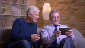 Ritratto degli amici maschii senior che si siedono insieme sul sofà che guarda nella compressa e che discute allegro archivi video