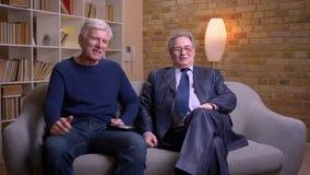 Ritratto degli amici maschii senior che si siedono insieme sul sofà che guarda TV e che discute allegro archivi video