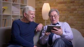 Ritratto degli amici maschii senior che si siedono insieme sul sof? che swiping le foto sulla compressa e che reagisce emozionalm video d archivio