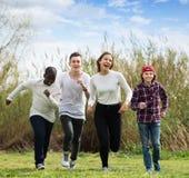 Ritratto degli amici sorridenti che corrono sul campo Immagini Stock Libere da Diritti