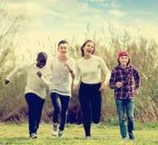Ritratto degli amici sorridenti che corrono sul campo Fotografia Stock Libera da Diritti