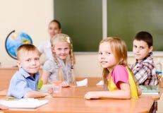 Ritratto degli scolari nel luogo di lavoro con l'insegnante su fondo Fotografia Stock Libera da Diritti