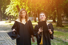 Ritratto degli studenti felici in abiti di graduazione Fotografie Stock Libere da Diritti