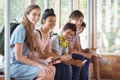 Ritratto degli studenti felici che si siedono sul davanzale della finestra e che utilizzano telefono cellulare nel corridoio Immagine Stock