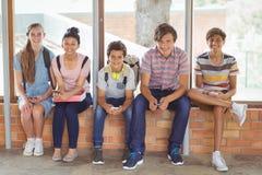 Ritratto degli studenti felici che si siedono sul davanzale della finestra e che utilizzano telefono cellulare nel corridoio Immagini Stock Libere da Diritti
