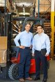 Ritratto degli uomini d'affari con il carrello elevatore a forcale in magazzino Immagini Stock