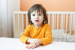 Ritratto dei 2 anni svegli di bambino che si siede alla tavola Immagini Stock Libere da Diritti
