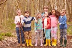 Ritratto dei bambini che giocano il gioco di avventura in foresta fotografia stock libera da diritti