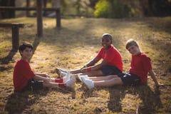 Ritratto dei bambini felici che si rilassano sull'erba durante la corsa ad ostacoli immagine stock