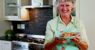 Ritratto dei biscotti senior della tenuta della donna in piatto 4k video d archivio