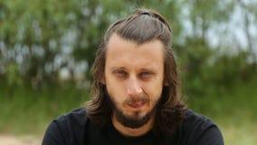 Ritratto dei capelli lunghi e della barba di un giovane tipo sulla via in cui sta facendo i fronti stock footage