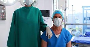 Ritratto dei chirurghi che indossano il teatro in funzione della maschera chirurgica stock footage