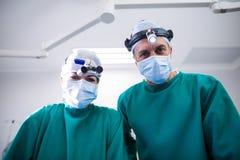 Ritratto dei chirurghi con la stanza in funzione delle lenti di ingrandimento chirurgiche Fotografia Stock Libera da Diritti